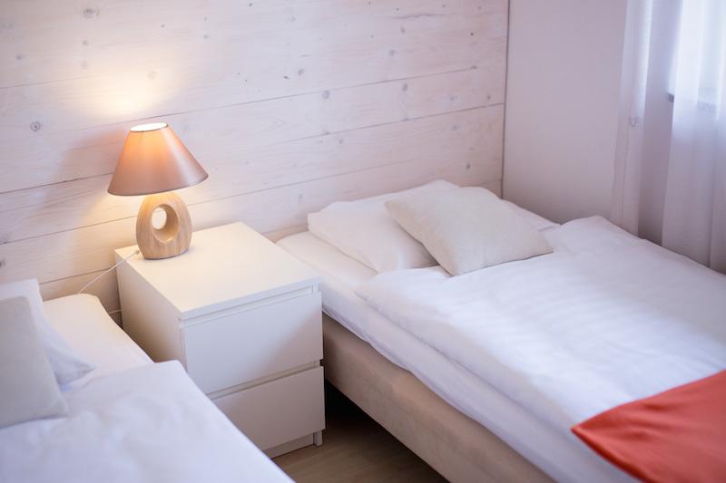 Pokój z łóżkami szafką i lampką