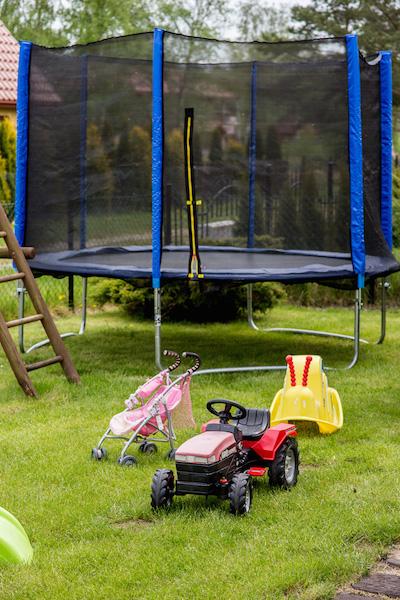 podwórze dla dzieci z trampoliną i zabawkami